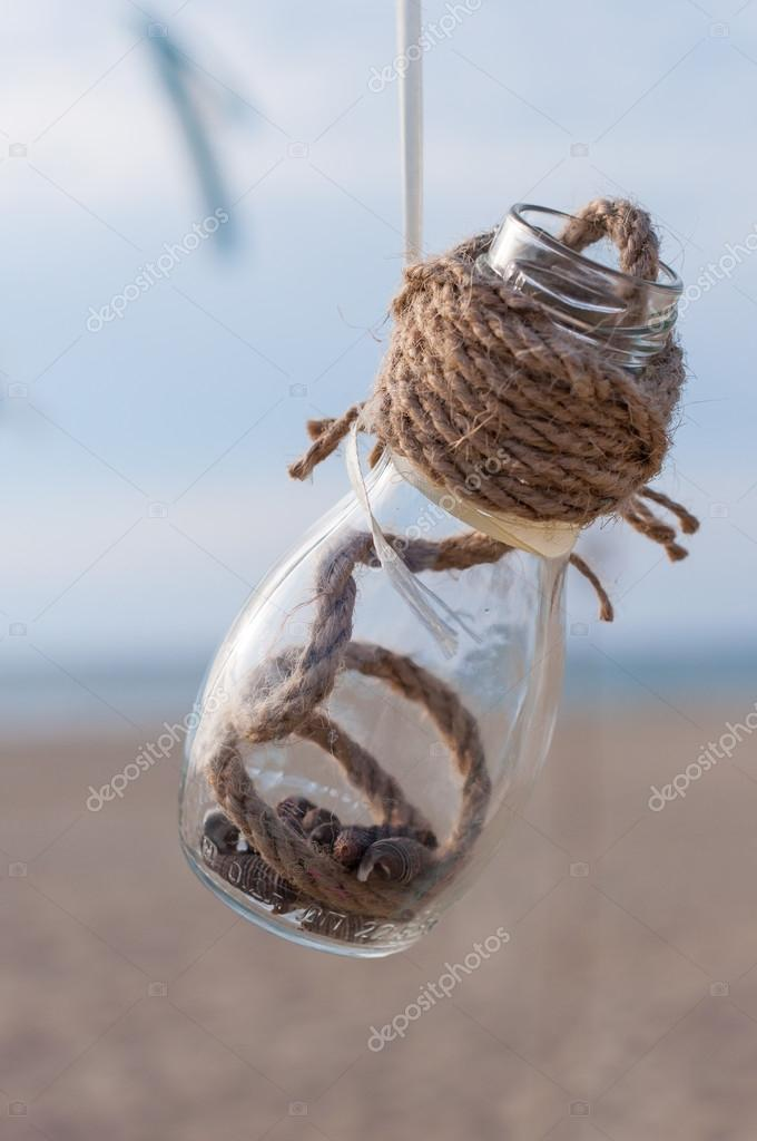 Seashells in a jar on the beach, vintage decor