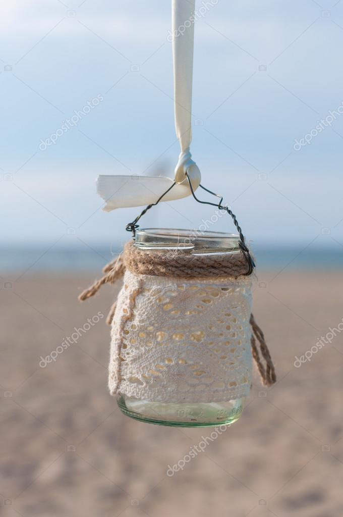 jar with lace for candle on the beach and sea background, vintage decor