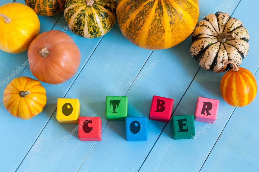 October sign on color wooden cubes with light blue wood background.