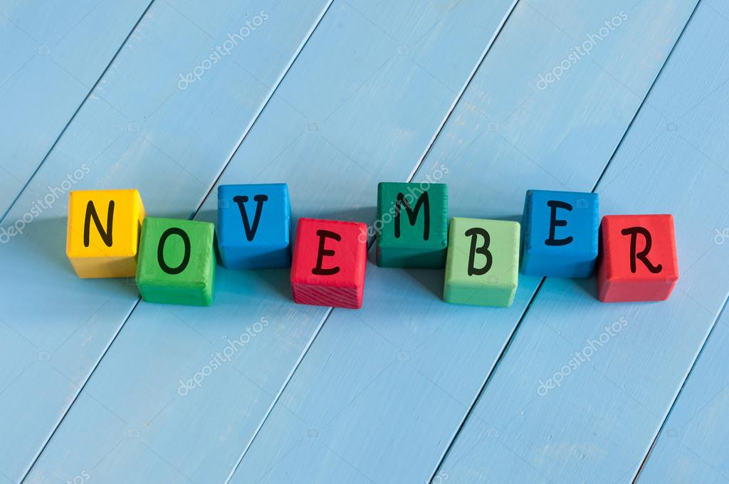Word November On childs toy cubes on wooden rural  background.