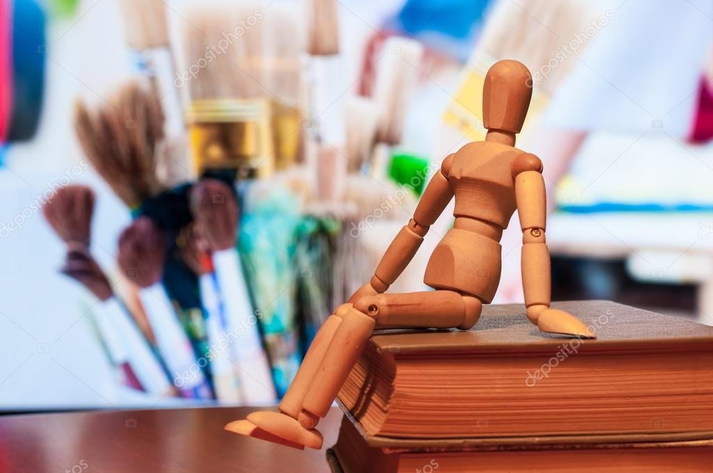 Wooden dummy, mannequin or man figurine sit on book with many brushes On background