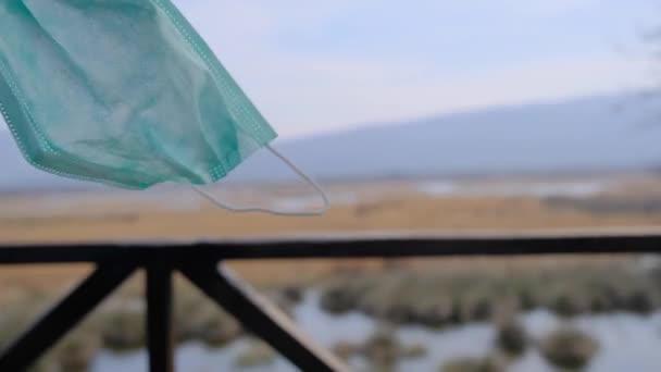 Ein Mann, der vom Vogelbeobachtungsturm auf die Karacabey-Aue blickt, und er hat die grüne medizinische Maske wegen der covid 19 Pandemie abgelegt und geht dann zurück und beobachtet die Naturszene als Berg, Sumpf, Wasser.