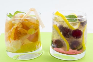 Peach and raspberry juices with fruit slices in a crooked glass