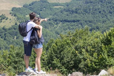 Couple of hikers with backpacks standing at viewpoint and enjoyi