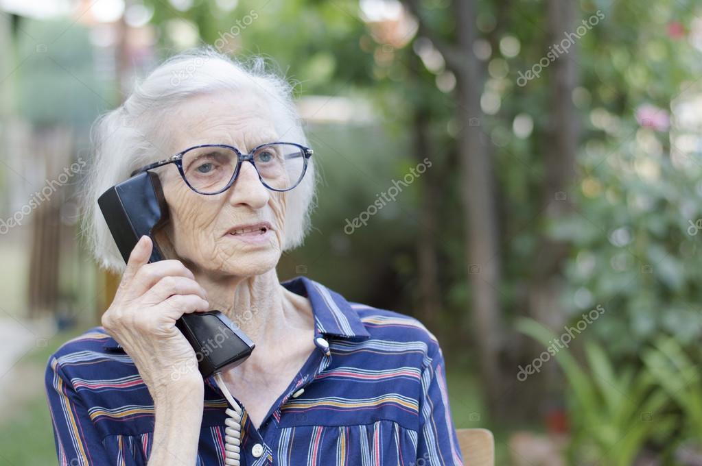 老婦人の家の裏庭に電話で話して...