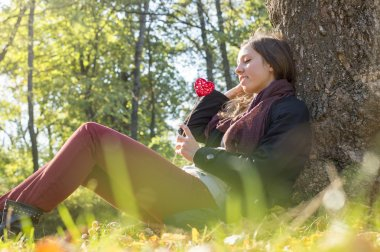 Beautiful girl holding red heart on a stick while sitting on the