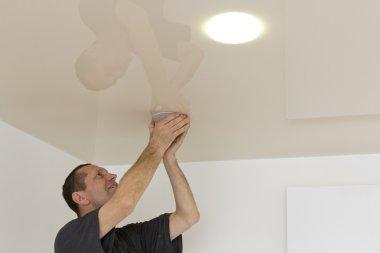 Electrician installs neatly spotlight.