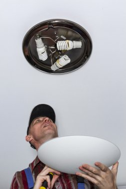 Electrician installs lighting the lamp on the ceiling of the room.