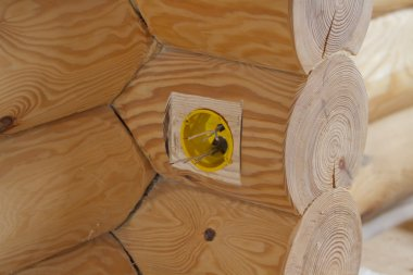 Holes for the electrical outlets in a log house.