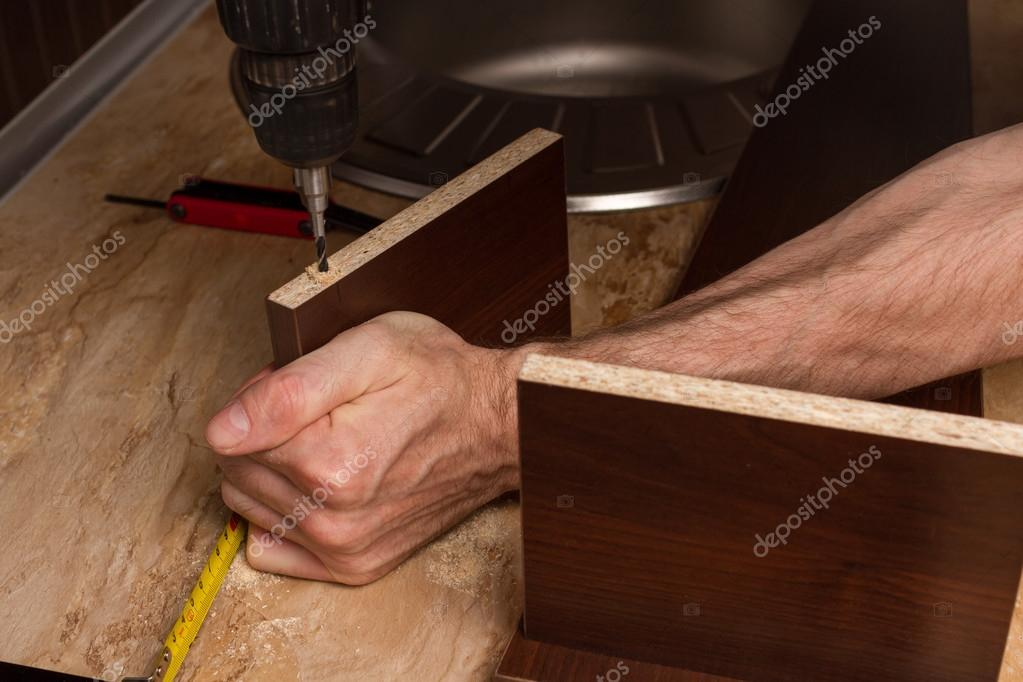 Furniture parts during drilling in the hands of builder of furniture.
