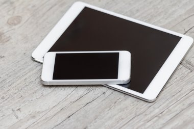 smartphone and tablet on the gray wooden background