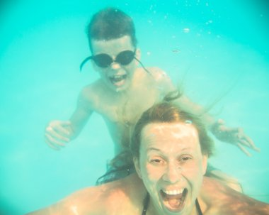 Mother and son grimace under water in the pool