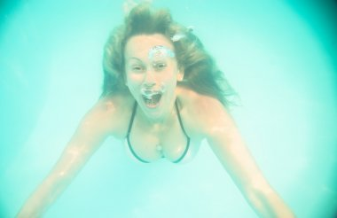 Woman swimming underwater in the pool