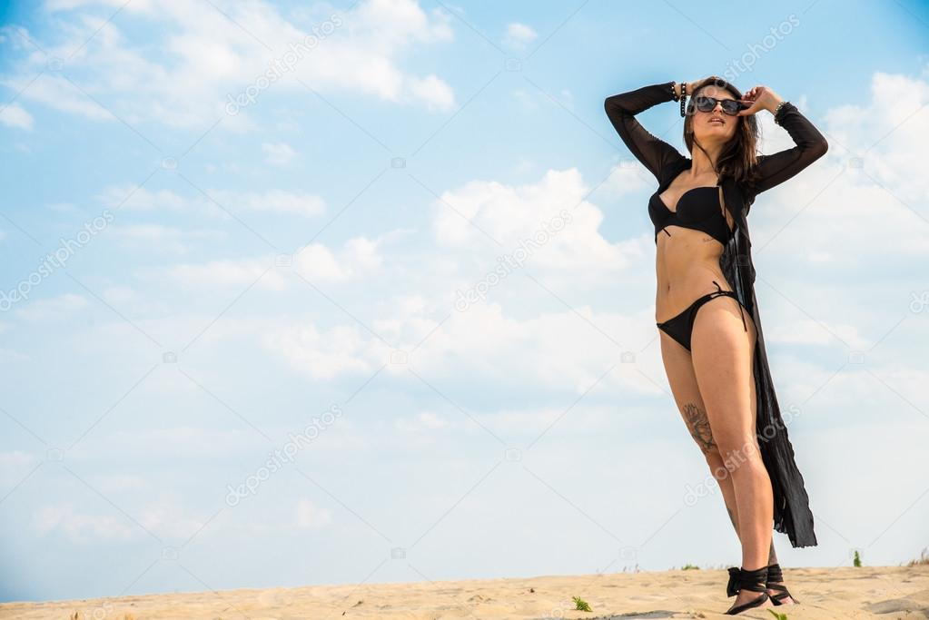 Girl in black swimsuit jumping on the background of the desert