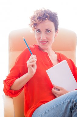 Girl sitting on a leather chair and holding a pencil and notepad