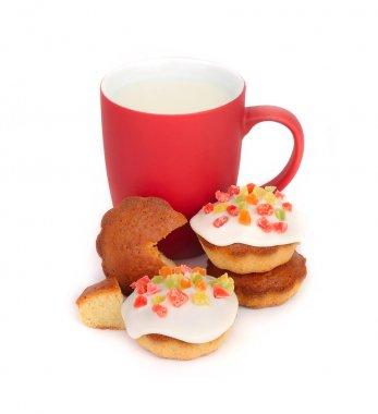 Red cup with milk and small biscuits with confectionery mastic on a white background.