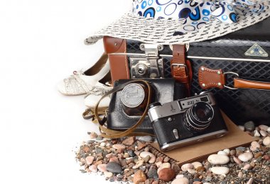 Old suitcase, the camera and hat on a white background. Retro travel.