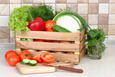 The fresh washed-up vegetables in a wooden box and the cut vegetables on a chopping board against modern kitchen.