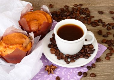 Cup of coffee and fragrant fresh house cakes on a wooden background.