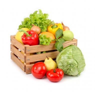 Fresh vegetables and fruit in a wooden box on a white background.