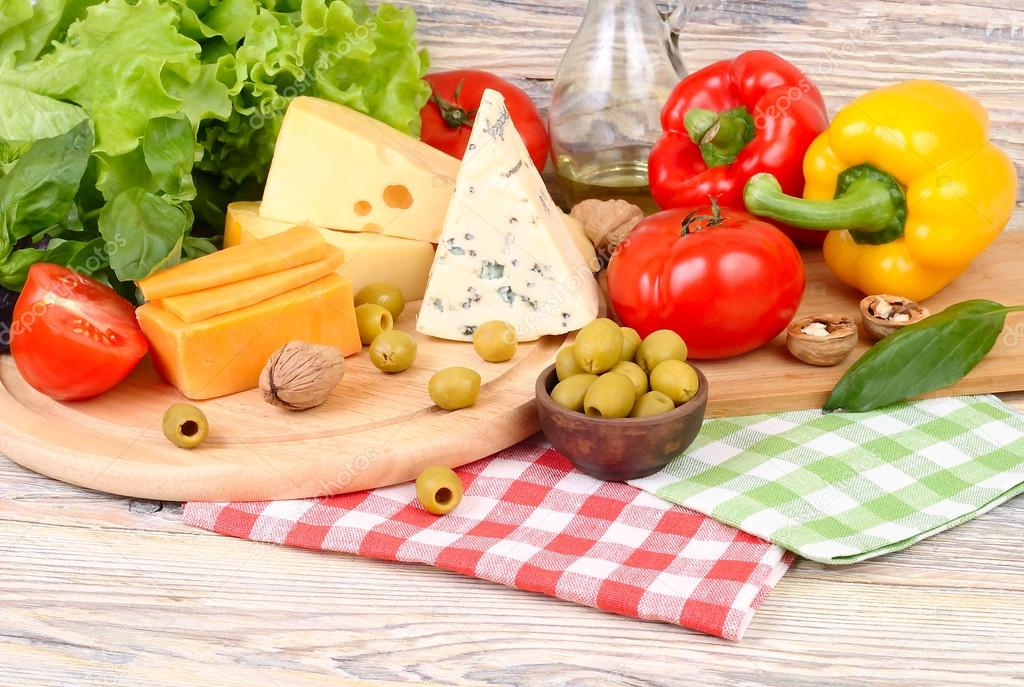 Cheese of various grades, fresh vegetables and olives on a light wooden background. Ingredients for preparation of the Italian vegetarian pizza.