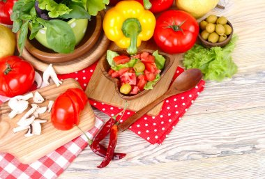 Fresh vegetables and mushrooms on a wooden background. Top view.