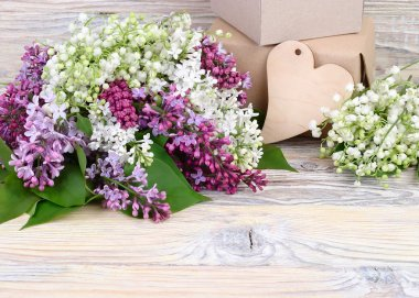 Charming spring flowers of a lilac and lilies of the valley and gift boxes on a wooden background. A background for the subject