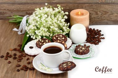 Cup of fragrant coffee with cookies and a bunch of lilies of the valley on a white background.