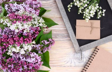 Flower wooden background with a lilac and a cretaceous board with a place for the text. Top view.