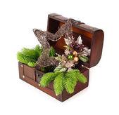 Dřevěná truhla s dekorativní hvězda a větve vánočního stromku na bílém pozadí. Vánoční pozadí