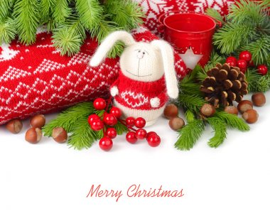 Knitted hare, nuts and cones near knitted pillows and branches of a Christmas tree on a white background. Christmas background.