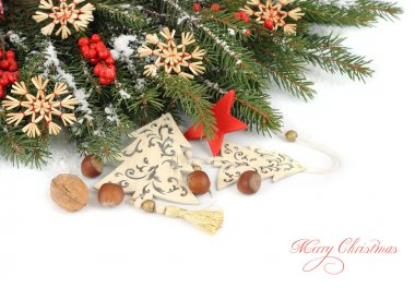 Decorative Christmas fir-trees on branches of a Christmas tree on a white background. A Christmas background with a place for the text.