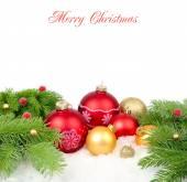 Červené a zlaté vánoční koule na větvích vánočního stromku na bílém pozadí. Vánoční pozadí s místem pro text