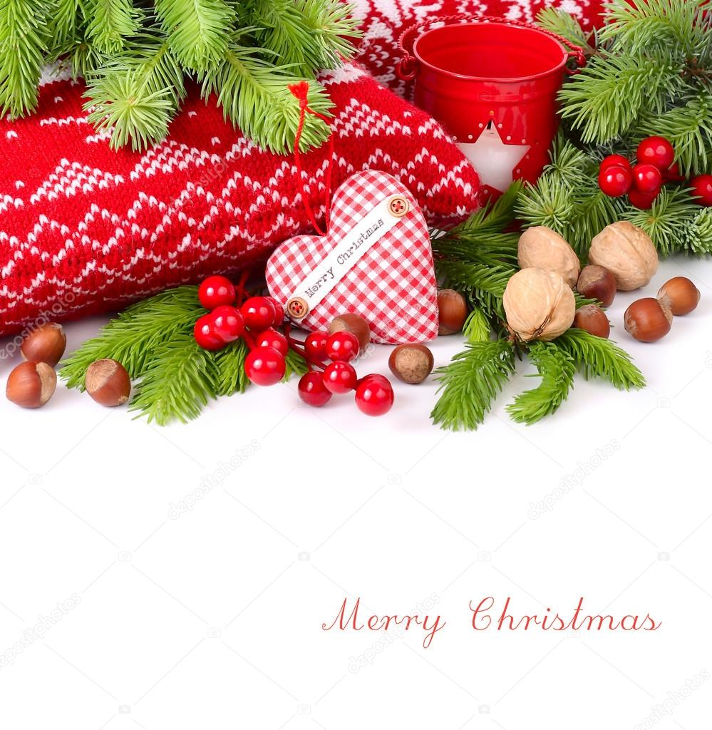 Textile checkered heart, nuts and red berries near knitted pillows and branches of a Christmas tree on a white background. A Christmas background with a place for the text.