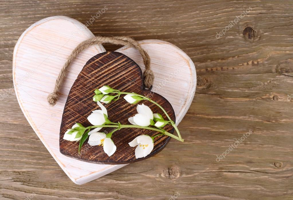 Two wooden hearts and branch of a jasmine on a wooden background. A background for the subject