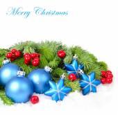 Modrý vánoční koule a hvězdy a červené bobule na větvích vánočního stromku na bílém pozadí. Vánoční pozadí s místem pro text