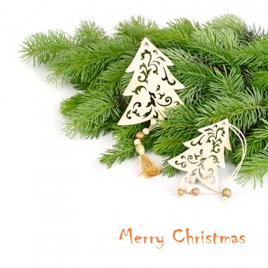 Wooden openwork fir-trees on fluffy branches of a Christmas tree on a white background. A Christmas background with a place for the text.