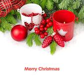 Červené a bílé svícny, vánoční koule a šišky na větvích vánočního stromku na bílém pozadí. Vánoční pozadí s místem pro text