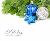 Modré a stříbrné vánoční koule a modrá hvězda na nadýchané větve vánočního stromku na bílém pozadí. Vánoční pozadí s místem pro text