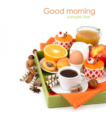 Breakfast for every taste in a tray: coffee, fruit, juice, boiled egg, cakes and wafer tubules on a white background with a place for the text.