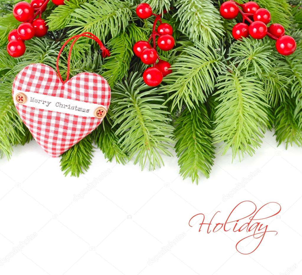 Red berries and red checkered textile heart on fluffy branches of a Christmas tree on a white background. A Christmas background with a place for the text.
