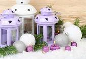 Fialový svícny - lampy a fialová a bílá vánoční koule sněhu na bílém pozadí. Vánoční pozadí s místem pro text