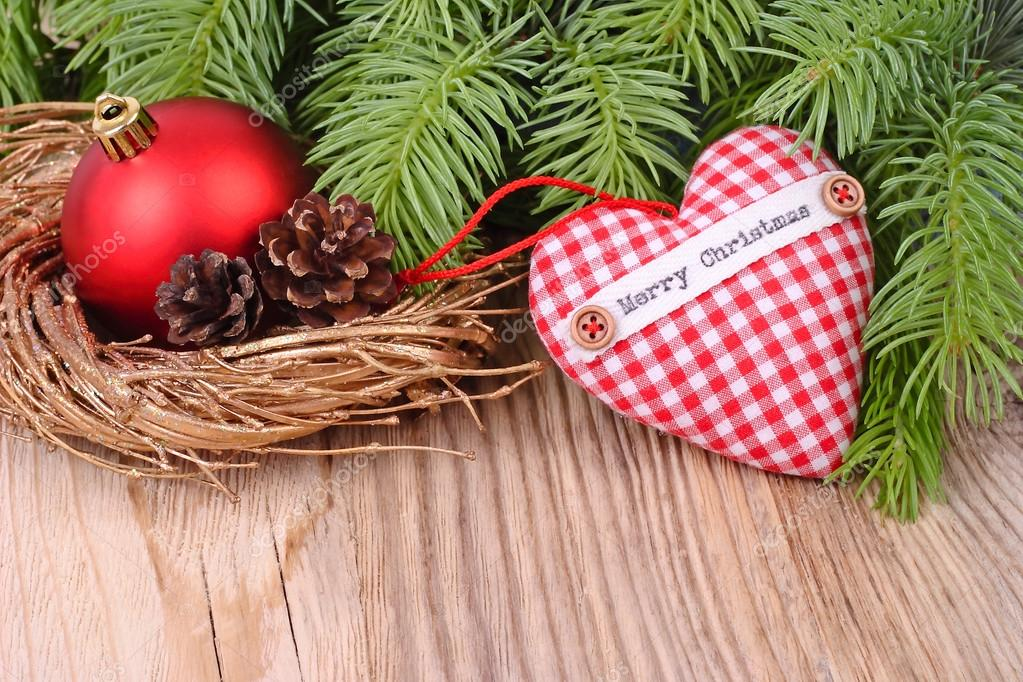 Red checkered textile heart and Christmas-tree decorations on branches of a Christmas tree on a wooden background. A Christmas background with a place for the text.