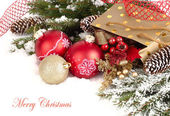 Christmas composition with branches of a Christmas tree, red and golden Christmas balls and cones on a white background. A Christmas background with a place for the text.