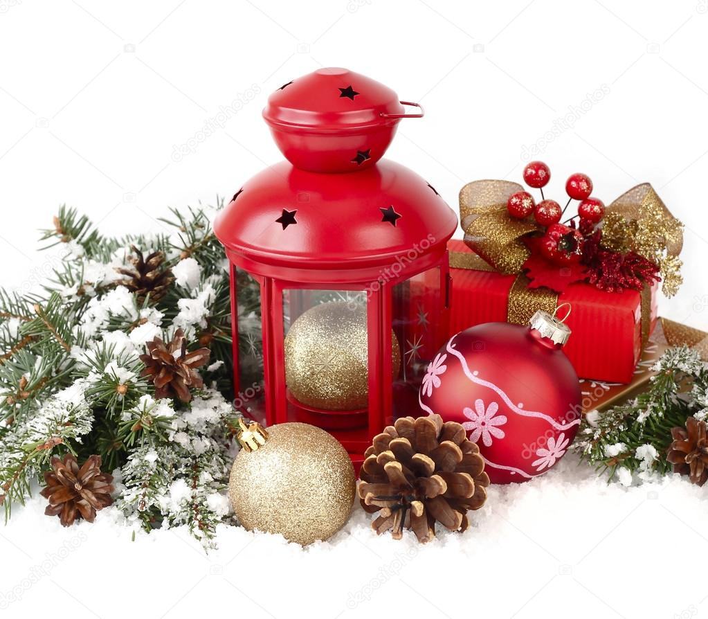 Red lamp candlestick, red and golden Christmas balls and cones on branches of a Christmas tree on a white background. A Christmas background with a place for the text.