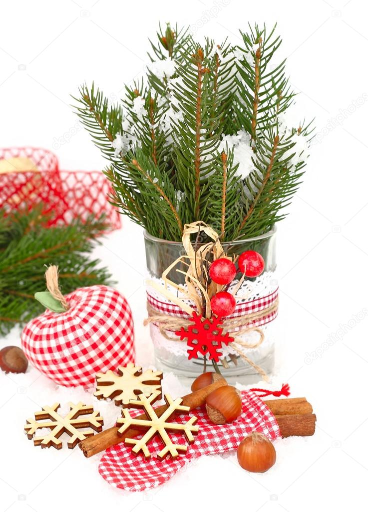 Textile checkered Christmas jewelry, wooden snowflakes and nuts on snow on a white background. A Christmas background with a place for the text.