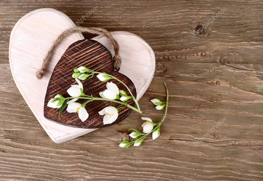 Two wooden hearts and branch of a jasmine on a wooden background. A background for St. Valentine's Day.