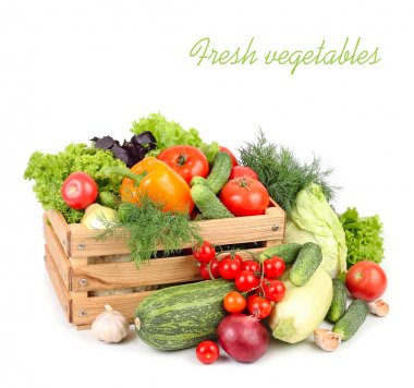Fresh ripe vegetables in a wooden box on a white background with a place for the text.