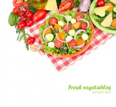 The Greek salad with cheese balls on an orange plate on a red checkered napkin and fresh ripe vegetables and herbs on a white background with a place for the text.