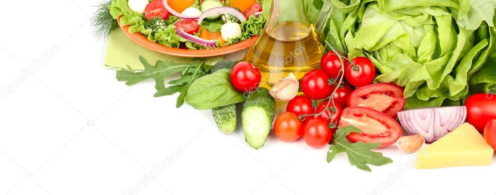 Fresh ripe vegetables and herbs and the Greek salad with cheese balls on an orange plate and on a white background with a place for the text.